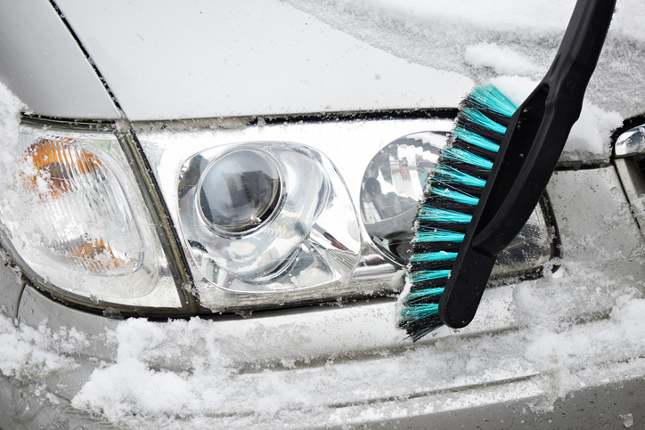 Man cleans a car from the snow with a brush